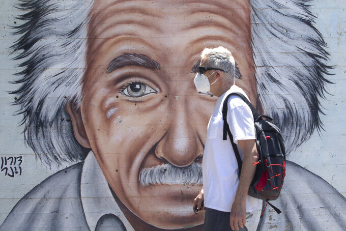 An Israeli man wearing a mask to curb the spread of the coronavirus walks past a mural showing Albert Einstein in Tel Aviv, Israel, Wednesday, July 15, 2020. (AP Photo/Sebastian Scheiner)