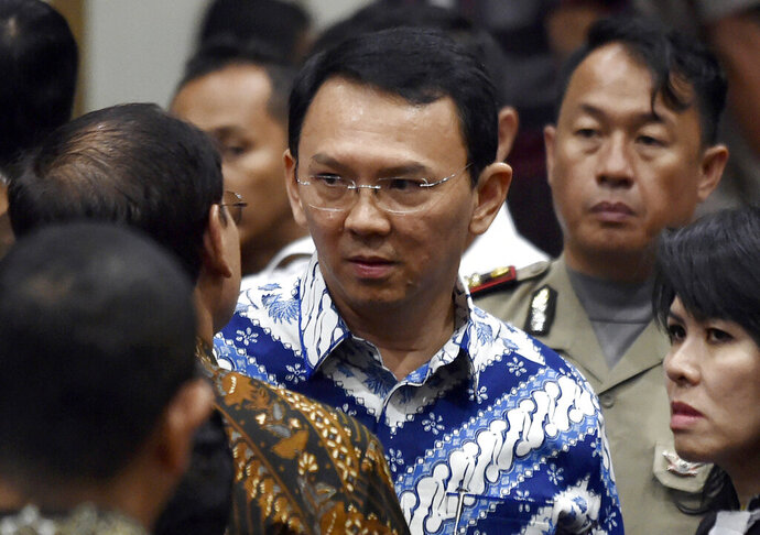 "FILE - In this May 9, 2017, file photo, then Jakarta Governor Basuki ""Ahok"" Tjahaja Purnama, center, talks to his lawyers after his sentencing hearing at a court in Jakarta, Indonesia, Tuesday, May 9, 2017.  The polarizing Christian politician whose campaign comments ignited protests that were the largest in Muslim-majority Indonesia in years was freed Thursday, Jan. 24, 2019 after serving nearly two years in prison for blasphemy. (Bay Ismoyo/Pool Photo via AP, File)"