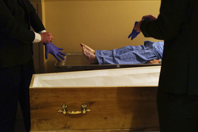 FILE - In this April 24, 2020 file photo, pallbearers, Louis Mercier, right, and Allan Pottier, left, prepare to carry the body of a 105-year-old woman as they prepare her for a funeral at a mortuary, in Paris. France is expected Thursday April 15, 2021, to pass the grim milestone of 100,000 COVID-19 deaths, after a year of hospital tensions, on-and-off lockdowns and personal loss that have left families nationwide grieving the pandemic's unending, devastating toll. (AP Photo/Francois Mori, File)