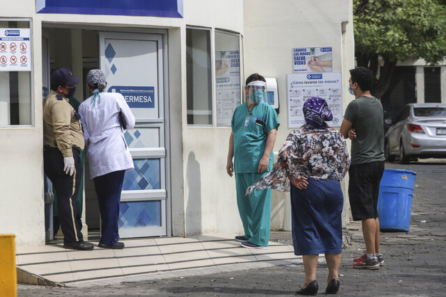 A medical worker wears a mask and a face shield at the entrance of the SERMESA hospital in Managua, Nicaragua, Monday, May 11, 2020. President Daniel Ortega's government has stood out for its refusal to impose measures to halt the new coronavirus for more than two months since the disease was first diagnosed in Nicaragua. Now, doctors and family members of apparent victims say, the government has gone from denying the disease's presence in the country to actively trying to conceal its spread. (AP Photo/Alfredo Zuniga)