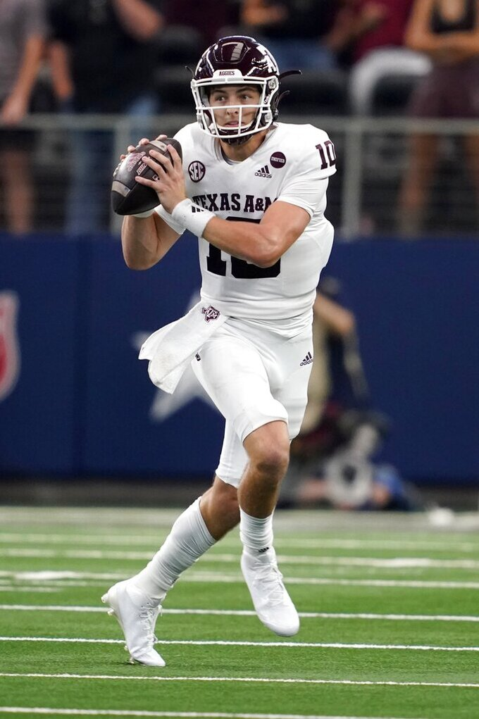 Texas A&M quarterback Zach Calzada scrambles out of the pocket before throwing a pass in the first half of an NCAA college football game against Arkansas in Arlington, Texas, Saturday, Sept. 25, 2021. (AP Photo/Tony Gutierrez)