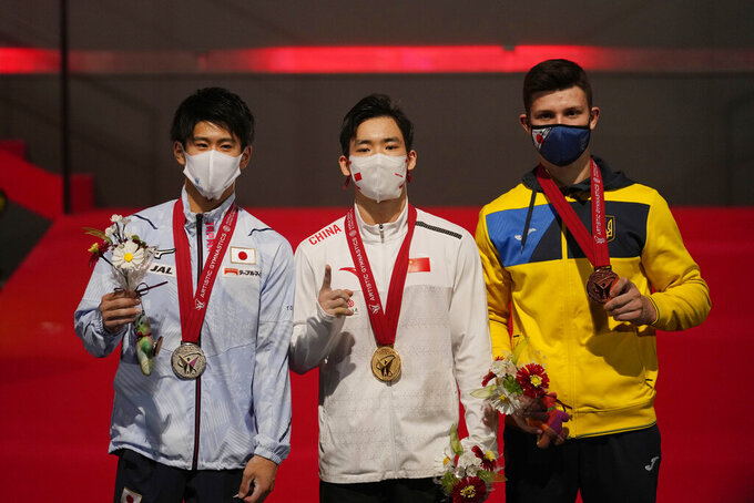 Zhang Boheng, center, of China, with his gold medal, Daiki Hashimoto, left, of Japan, with his silver medal, and Ilia Kovtun, of Ukraine, pose for photos and video during the podium ceremony after their men's all-around finals in the FIG Artistic Gymnastics World Championships in Kitakyushu, western Japan, Friday, Oct. 22, 2021. (AP Photo/Hiro Komae)