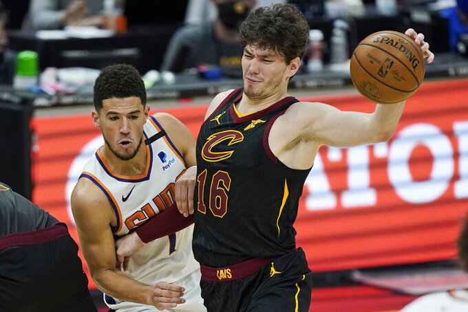 Cleveland Cavaliers' Cedi Osman, right, his fouled by Phoenix Suns' Devin Booker in overtime of an NBA basketball game, Tuesday, May 4, 2021, in Cleveland. Phoenix won 134-118 in overtime. (AP Photo/Tony Dejak)