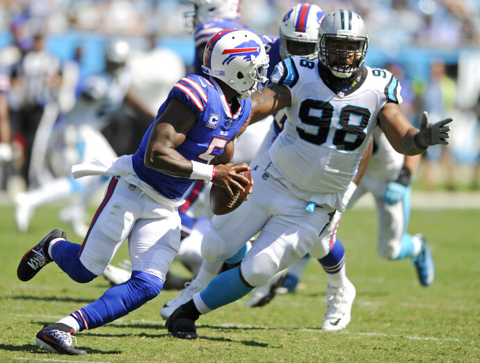 FILE - In this Sept. 17, 2017, file photo, Buffalo Bills' Tyrod Taylor (5) scrambles under pressure from Carolina Panthers' Star Lotulelei (98) in the second half of an NFL football game, in Charlotte, N.C. A person familiar with the situation confirms to The Associated Press that free agent defensive tackle Star Lotulelei has reached an agreement to sign a five-year contract with the Buffalo Bills. The person spoke on the condition of anonymity because the signing won't become official until the NFL's business year opens on Wednesday, March 14, 2018. (AP Photo/Mike McCarn, File)