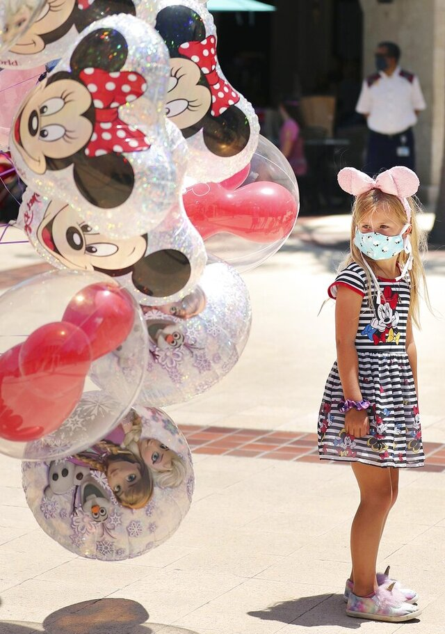 A girl gazes at Mickey Mouse balloons at Disney Springs in Orlando on Wednesday, May 20, 2020. Walt Disney World's sprawling shopping and dining complex is beginning the first phase of getting back to business with 44 establishments welcoming the public during the Coronavirus epidemic. (Stephen M. Dowell/Orlando Sentinel via AP)