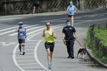 Runners pass a New York Police Officer as they warm weather during the coronavirus pandemic in Central Park Saturday, May 16, 2020, in New York. (AP Photo/Frank Franklin II)