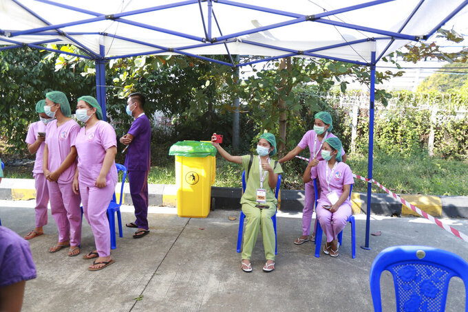 In this Jan. 27, 2021, file photo, Health workers wait to receive the Covishield COVID-19 vaccine at the Ayeyarwaddy COVID treatment center in Yangon, Myanmar. Medical workers across Myanmar have begun a civil disobedience protest against Monday, Feb. 1, 2021's coup, pinning red ribbons and declaring they won't work for the military government.(AP Photo/Thein Zaw, File)