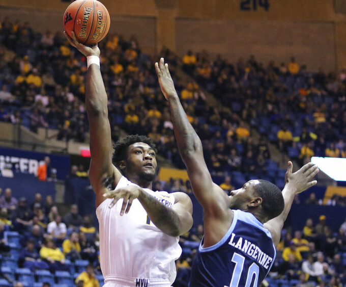West Virginia forward Derek Culver (1) goes to make a shot as he is defended by Rhode Island forward Cyril Langevine (10) during the second half of an NCAA college basketball game Sunday, Dec. 1, 2019, in Morgantown, W.Va. Culver scored 25 points against Rhode Island. (AP Photo/Kathleen Batten)