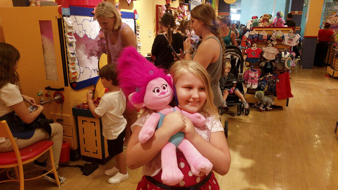Eight-year-old Skylar Baughey, of Clearwater, Fla., hugs her troll moments after completing its construction at the Build-A-Bear Workshop at Westfield Countryside Mall Thursday, July 12, 2018, in Clearwater, Fla. Baughey had stood in line with her family for more than four hours before gaining access to the store due to the overwhelming response to the event. The company wrote in a Facebook post that it closed lines at its stores in Canada and the U.S. due to overwhelming crowds and safety concerns. (Douglas R. Clifford/Tampa Bay Times via AP)