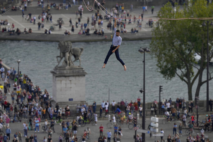 French slackliner Nathan Paulin performs on the second time on a 70-meter-high slackline between the Eiffel Tower and the Chaillot Theater across the Seine River, in Paris Sunday, Sept. 19, 2021. (AP Photo/Francois Mori)