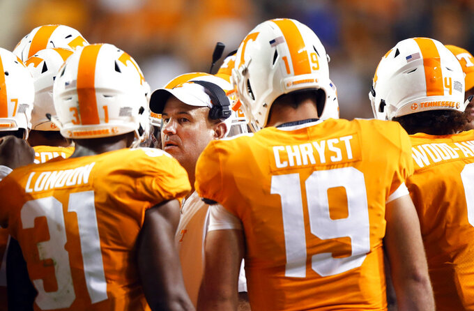 FILE- In this Sept. 22, 2018, file photo, Tennessee head coach Jeremy Pruitt, center, talks to his players in the second half of an NCAA college football game against Florida in Knoxville, Tenn. The Volunteers have lost 15 straight interdivisional games and haven't beaten an SEC West team since 2010. Tennessee will try to end that skid when it faces SEC West opponents each of the next two weeks, including a Saturday visit to No. 21 Auburn. (AP Photo/Wade Payne, File)