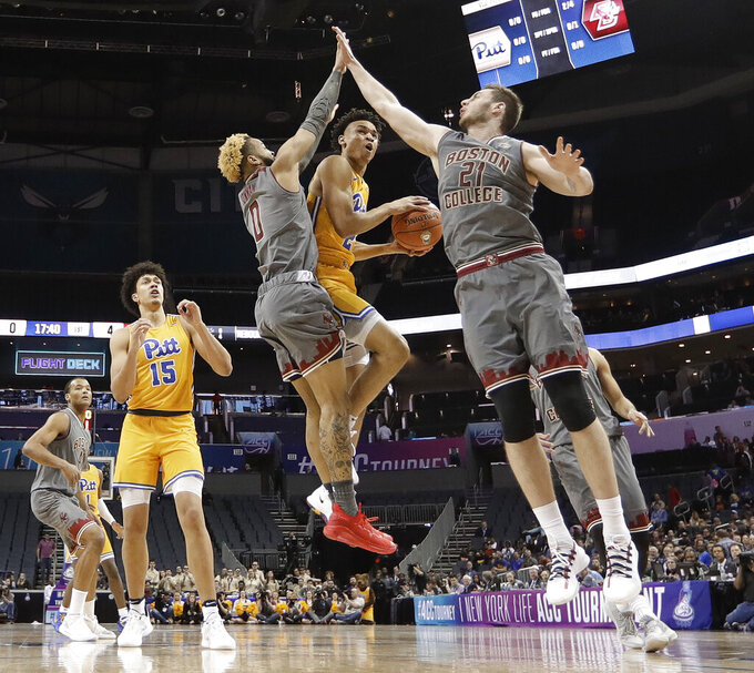 Pittsburgh's Trey McGowens (2) drives between Boston College's Nik Popovic (21) and Ky Bowman (0) during the first half of an NCAA college basketball game in the Atlantic Coast Conference men's tournament in Charlotte, N.C., Tuesday, March 12, 2019. (AP Photo/Nell Redmond)