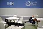 A visitor rests at the COP25 climate talks congress in Madrid, Spain, Saturday, Dec. 14, 2019. The United Nations Secretary-General has warned that failure to tackle global warming could result in economic disaster. (AP Photo/Manu Fernandez)