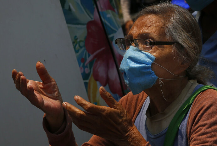 A woman waits for her meal from the mobile dining rooms program as people who have not been able to work because of the COVID-19 pandemic line up for a meal outside the Iztapalapa hospital in Mexico City, Wednesday, May 20, 2020. (AP Photo/Marco Ugarte)