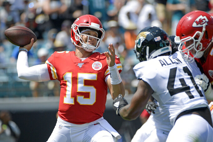 "FILE - In this Sunday, Sept. 8, 2019, file photo, Kansas City Chiefs quarterback Patrick Mahomes (15) throws a pass as he is pressured by Jacksonville Jaguars defensive end Josh Allen during the first half of an NFL football game in Jacksonville, Fla. The Chiefs visit the Raiders on Sunday, and that means one last trip to the ""Black Hole"" of what is generally known as Oakland–Alameda County Coliseum. (AP Photo/Phelan M. Ebenhack, File)"
