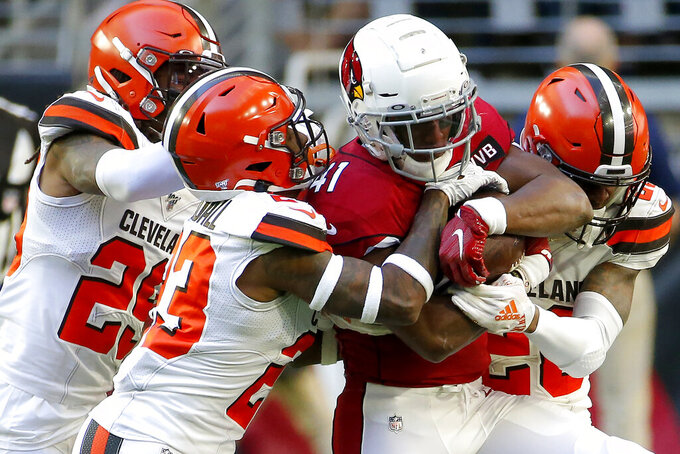 Arizona Cardinals running back Kenyan Drake, center, is tackled by Cleveland Browns free safety Damarious Randall, left, and Cleveland Browns cornerback Greedy Williams, right, during the first half of an NFL football game, Sunday, Dec. 15, 2019, in Glendale, Ariz. (AP Photo/Rick Scuteri)