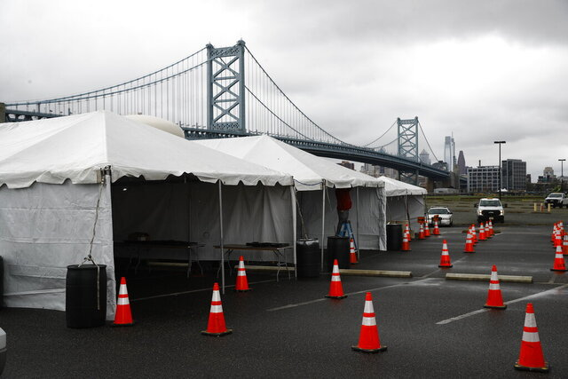 A drive-thru COVID-19 testing facility is set up in Camden, N.J., Tuesday, March 31, 2020, in view of the Benjamin Franklin Bridge. The newly erected facility is scheduled to open Wednesday. (AP Photo/Matt Rourke)