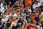 Fans try for a home run ball by Washington Nationals' Anthony Rendon during the seventh inning of Game 6 of the baseball World Series against the Houston Astros Tuesday, Oct. 29, 2019, in Houston. (AP Photo/Sue Ogrocki)
