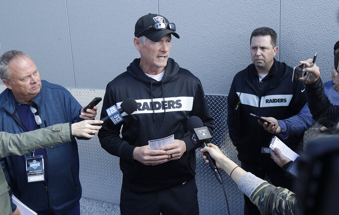 Oakland Raiders general manager Mike Mayock, center, speaks to reporters during an official team activity at the NFL football team's headquarters in Alameda, Calif., Tuesday, May 28, 2019. (AP Photo/Jeff Chiu)