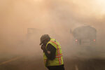 Len Brongo struggles with smoke from the Silverado Fire Monday, Oct. 26, 2020, in Irvine, Calif. (AP Photo/Jae C. Hong)