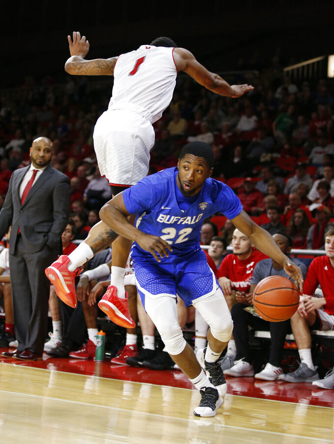 Buffalo guard Dontay Caruthers (22) slips around the defensive efforts of Miami (Ohio) guard Nike Sibande (1) during the first half of an NCAA college basketball game, Friday, March 1, 2019, in Oxford, Ohio. (AP Photo/Gary Landers)