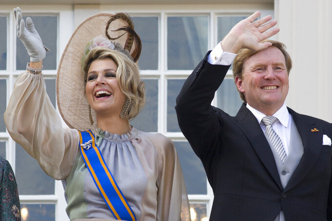 """FILE - In this Tuesday, Sept. 18, 2018, file photo, Dutch King Willem-Alexander and Queen Maxima wave from the balcony of royal palace Noordeinde in The Hague, Netherlands, after a ceremony marking the opening of the parliamentary year with a speech by King Willem-Alexander outlining the government's budget plans for the year ahead. The Dutch king issued a video message Wednesday saying """"with sorrow in the heart"""" that he regrets flying to Greece for a family vacation last week, a trip that was quickly broken off amid public uproar back home where people are being urged to stay home as much as possible to battle the coronavirus. (AP Photo/Peter Dejong, File)"""