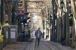 A pedestrian wears a mask while standing on train tracks during the coronavirus pandemic in San Jose, Calif., Tuesday, Dec. 1, 2020. (AP Photo/Jeff Chiu)