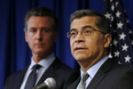 FILE - In this Sept. 18, 2019, file photo California Attorney General Xavier Becerra, right, speaks next to Gov. Gavin Newsom during a news conference in Sacramento, Calif. Opening arguments begin Thursday, Oct. 10, 2019, in the antitrust case against Sutter Health, one of California's largest hospital systems, which is facing a trial over accusations that it has used its market dominance to snuff out competition and overcharge patients for medical bills. (AP Photo/Rich Pedroncelli, File)