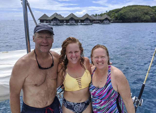Kristen Pankratz, center, poses with her parents David and Anne on their yacht Amazing Grace in Tahiti on April, 23, 2020. Pankratz gave up her advertising job in Dallas and set sail with her parents in January. But now, along with hundreds of other sailors, the family finds themselves stranded in paradise. They made it as far as Tahiti in remote French Polynesia, one of the last places to offer refuge as borders slammed shut. (Kristen Pankratz via AP)