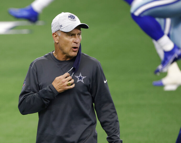 FILE - In this Oct. 11, 2020, file photo, Dallas Cowboys defensive coordinator Mike Nolan talks to players as they warm up for an NFL football game against the New York Giants in Arlington, Texas. The Cowboys have fired Nolan after their defense allowed a franchise record in points and finished 31st in the NFL against the run in his only season, the team announced Friday, Jan. 8, 2021. (AP Photo/Ron Jenkins, File)