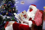 FILE - In this Monday, Nov. 23, 2020 file photo, a postal worker dressed as Santa, reads letters to addressed to