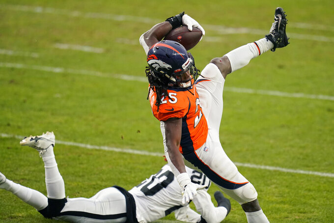 Denver Broncos running back Melvin Gordon (25) is tackled by Las Vegas Raiders cornerback Damon Arnette (20) during the first half of an NFL football game, Sunday, Jan. 3, 2021, in Denver. (AP Photo/Jack Dempsey)