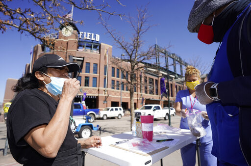 Martha Bravo, left, self-administers a swab COVID-19 test under the guidance of Josh Copeland at a table set up outside the main gate of Coors Field as fans return for the first time to the ballpark for a baseball game between the Los Angeles Dodgers and the Colorado Rockies Thursday, April 1, 2021, in Denver. Community Wellness of America was offering the service to fans as they entered the ballpark. (AP Photo/David Zalubowski)