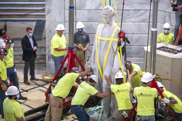 Workers prepare to remove the Jefferson Davis statue from the Kentucky state Capitol in Frankfort, Ky., on Saturday, June 13, 2020. A Kentucky commission voted to take down a statue of Confederate President Jefferson Davis from the state Capitol. The panel supported a push from the governor as the country faces protests against police brutality following the deaths of African Americans in encounters with police. (Ryan C. Hermens/Lexington Herald-Leader via AP)