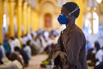 In this photo taken Friday, May 15, 2020, a follower of the Senegalese Mouride brotherhood, an order of Sufi Islam, cries as he and others attend Muslim Friday prayers at West Africa's largest mosque the Massalikul Jinaan, in Dakar, Senegal. A growing number of mosques are reopening across West Africa even as confirmed coronavirus cases soar, as governments find it increasingly difficult to keep them closed during the holy month of Ramadan. (AP Photo/Sylvain Cherkaoui)