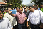 U.S. Senator Marco Rubio, R-Fla., in sunglasses, poses for photos with people near the Simon Bolivar International Bridge, which connects Colombia with Venezuela, in La Parada, near Cucuta, Colombia, Sunday, Feb. 17, 2019. As part of U.S. humanitarian aid to Venezuela, Rubio is visiting the area where the medical supplies, medicine and food aid is stored before it it expected to be taken across the border on Feb. 23. (AP Photo/Fernando Vergara)