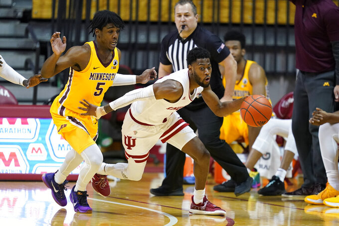 Indiana's Al Durham (1) is chased by Minnesota's Marcus Carr (5) during the second half of an NCAA college basketball game, Wednesday, Feb. 17, 2021, in Bloomington, Ind. Indiana won 82-72. (AP Photo/Darron Cummings)
