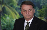 FILE - In this Oct. 1, 2019 file photo, President Jair Bolsonaro attends a ceremony to launch an agro program at the Planalto presidential palace in Brasilia, Brazil. Alter do Chao, a sleepy Amazon town, has become the flashpoint for the growing hostility between Bolsonaro and environmental groups following the arrest of firefighters he says set rainforest fires. (AP Photo/Eraldo Peres, File)