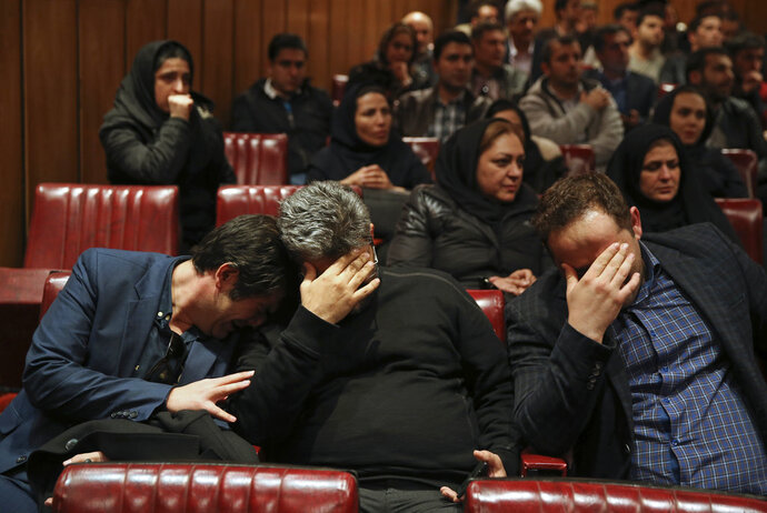 Friends and colleagues of the deceased Iranian seafarers aboard a tanker that sank off the coast of China weep at the headquarters of National Iranian Tanker Company, in Tehran, Iran, Sunday, Jan. 14, 2018. The burning Iranian tanker listing for days off the coast of China after a collision with another vessel sank Sunday, with an Iranian official saying there was