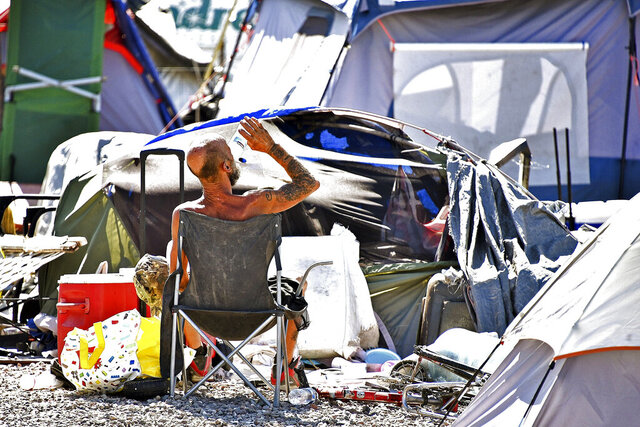 A homeless man sits by his belongings at the Lots, a county-run outdoor encampment in downtown Phoenix, on June 24, 2020. Homeless people are among the most vulnerable populations in the COVID-19 pandemic, yet they're largely invisible victims. Very little is known about how they're faring. The U.S. Department of Housing and Urban Development, which oversees homeless programs, has not required its national network of providers to gather infection or death data, even though homeless people, unlike other high-risk groups such as nursing home residents, interact more with the public. (Steve Carr/Human Services Campus and the Howard Center For Investigative Journalism via AP)