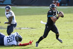 Jacksonville Jaguars quarterback Gardner Minshew II (15) scrambles away from Tennessee Titans defensive tackle Jeffery Simmons (98) during the second half of an NFL football game, Sunday, Dec. 13, 2020, in Jacksonville, Fla. (AP Photo/Phelan M. Ebenhack)