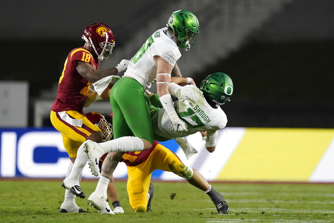 Oregon quarterback Cale Millen (17) is tackled by Southern California safety Talanoa Hufanga (15) and linebacker Raymond Scott (18) during the second quarter of an NCAA college football game for the Pac-12 Conference championship Friday, Dec 18, 2020, in Los Angeles. Oregon tight end Spencer Webb (18) is center. (AP Photo/Ashley Landis)