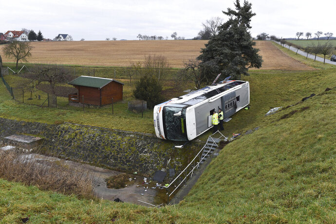 Police officers looks into a school bus that has crashed in Berka Vor Dem Hainich, near Eisenach, Germany, Thursday, Jan. 23, 2020. German media reported that two children died in a school bus crash in the central state of Thuringia early Thursday. Public broadcaster MDR reported that 20 children and the bus driver were injured in the crash in Berka, about 260 kilometers (160 miles) southwest of Berlin. (Swen Pfoertner/dpa via AP)