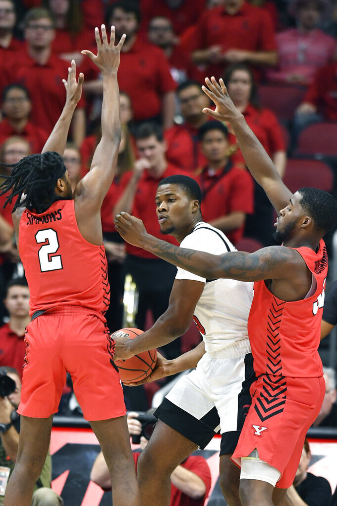 Louisville center Steven Enoch (23) looks for help against the trapping defense of Youngstown State guard Jelani Simmons (2) and forward Naz Bohannon (33) during the first half of an NCAA college basketball game in Louisville, Ky., Sunday, Nov. 10, 2019. (AP Photo/Timothy D. Easley)