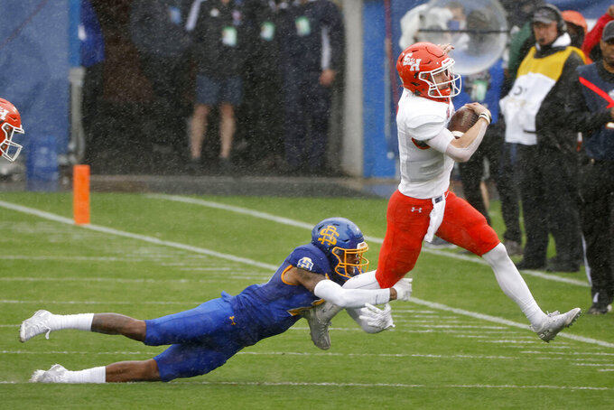 South Dakota State cornerback Don Gardner, left, tries to tackle Sam Houston State quarterback Eric Schmid, right during the first half of the NCAA college FCS Football Championship in Frisco, Texas, Sunday, May 16, 2021. (AP Photo/Michael Ainsworth)