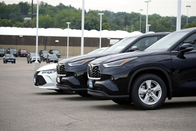 In this Sunday, Aug. 29, 2021, file photo, a pair of unsold 2021 Highlander sports utility vehicles and a Camry sedan are parked on the empty storage lot outside a Toyota dealership in Englewood, Colo. A global shortage of computer chips has forced automakers to temporarily close factories, limiting production and driving up prices. The coronavirus delta variant is now causing shortages of other parts. (AP Photo/David Zalubowski, File)