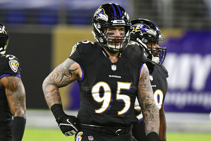 Baltimore Ravens defensive end Derek Wolfe (95) looks on during the first half of an NFL football game against the Dallas Cowboys, Tuesday, Dec. 8, 2020, in Baltimore. Wolfe, an energetic and talented defensive end, lost his passion for the game during a miserable four-year stretch in Denver that featured three head coaches, 37 defeats and not a single trip to the postseason. So he took a one-year deal with Baltimore, and now Wolfe and the Ravens are right where they want to be in the middle of January: still alive in the playoffs and very much in the running for a trip to the Super Bowl. (AP Photo/Terrance Williams, File)