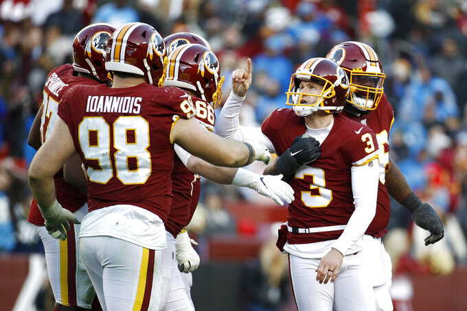Washington Redskins kicker Dustin Hopkins, center, gestures while being mobbed by teammates after kicking the eventual game-winning field goal in the final seconds of the second half of an NFL football game against the Detroit Lions, Sunday, Nov. 24, 2019, in Landover, Md. The Redskins won 19-16. (AP Photo/Patrick Semansky)