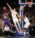 New York Knicks' Mario Hezonja (8), center, blocks what could have been the winning shot by Los Angeles Lakers' LeBron James, left, during the second half of the NBA basketball game, Sunday, March 17, 2019, in New York. (AP Photo/Seth Wenig)