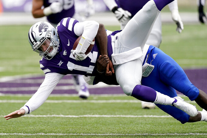 Kansas State quarterback Nick Ast (17) is sacked by Kansas linebacker Kyron Johnson (15) during the second half of an NCAA football game Saturday, Oct. 24, 2020, in Manhattan, Kan.  (AP Photo/Charlie Riedel)